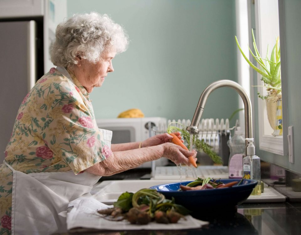 an elderly woman wearing a floral dress and an apron washes vegetables in her sink