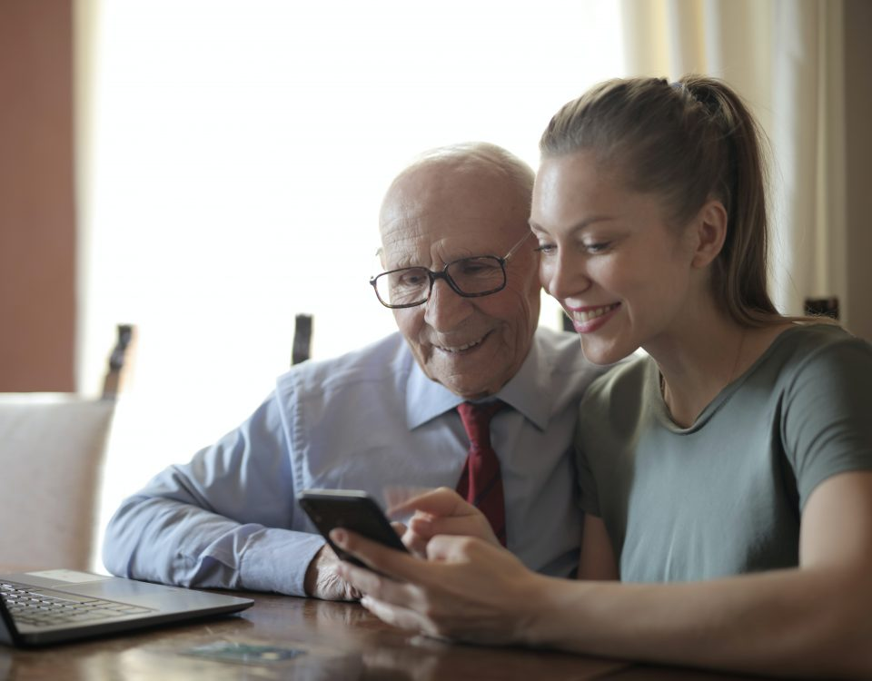 an elderly man looks at a photo on a phone with a young woman. They are both smiling