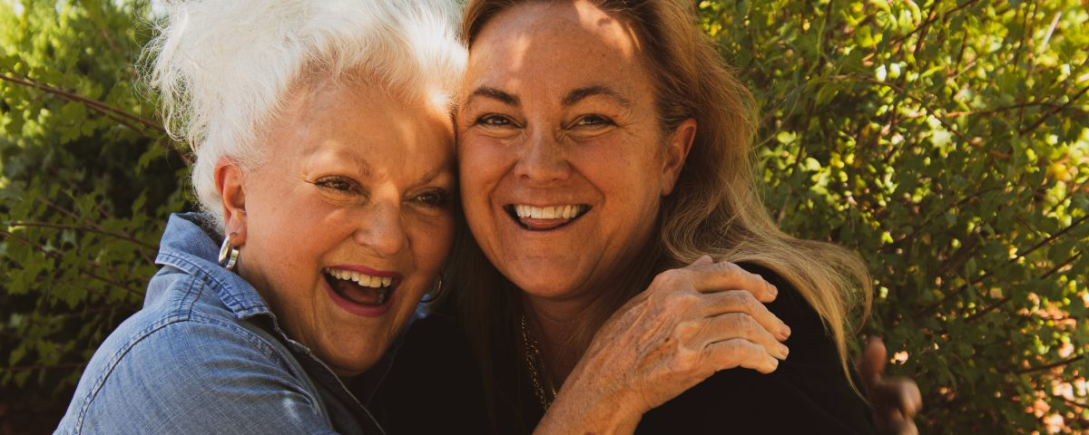 a woman and her elderly parent embrace and smile